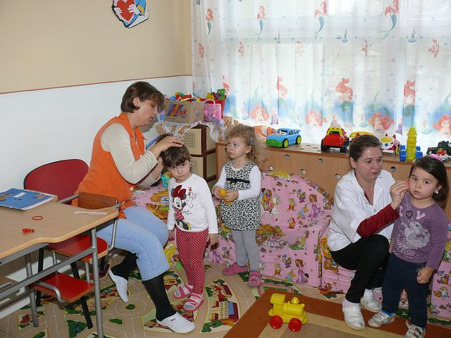 two women assisting and teaching children in a child care center
