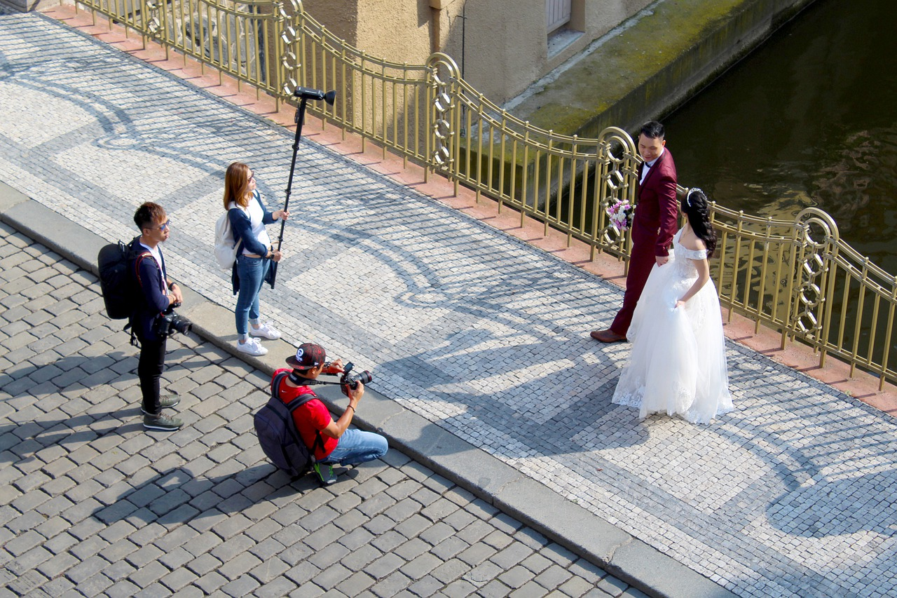 Wedding photographer and his team taking prenup photos with the couple. Source Pixabay