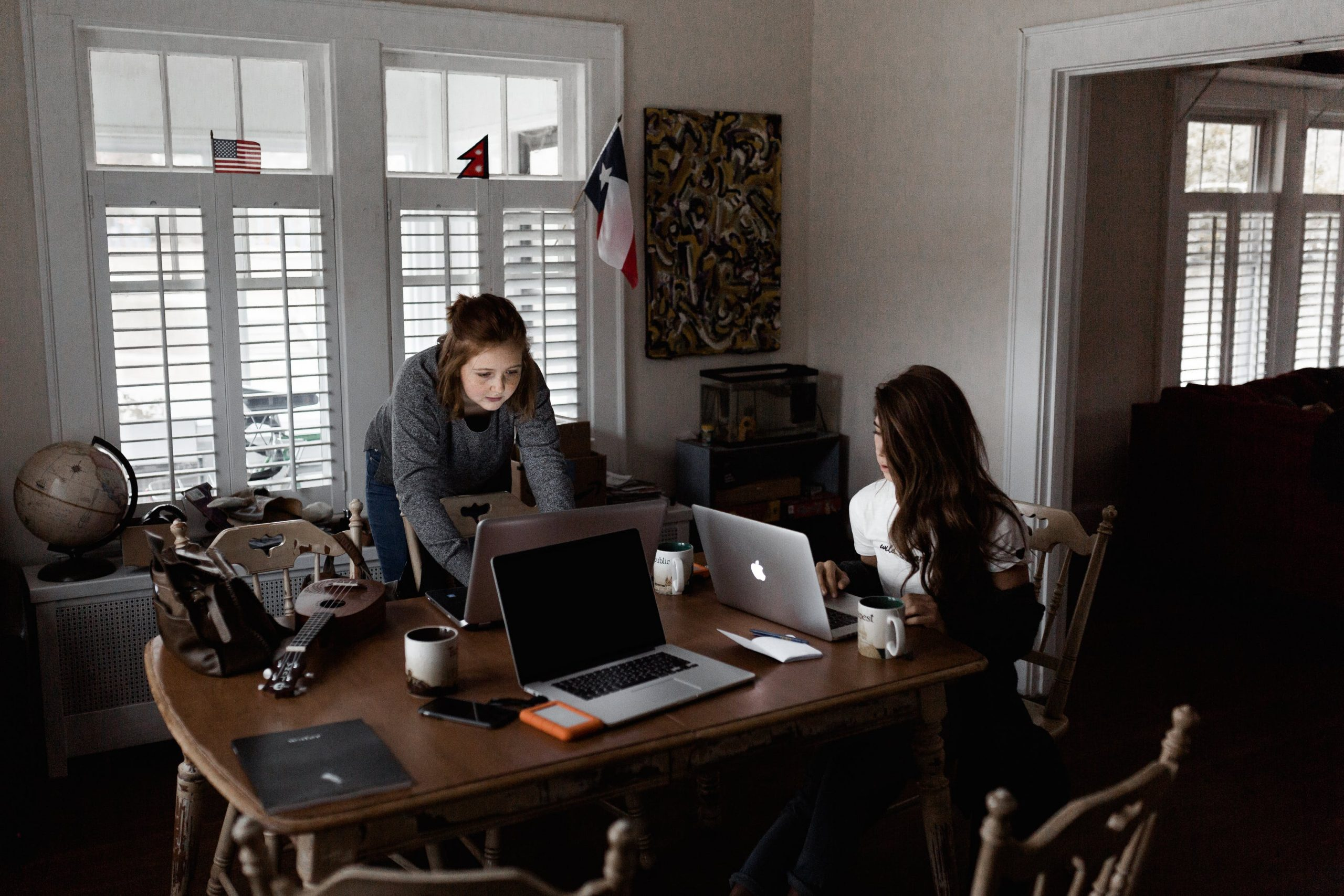 two women while working in a big partners desk